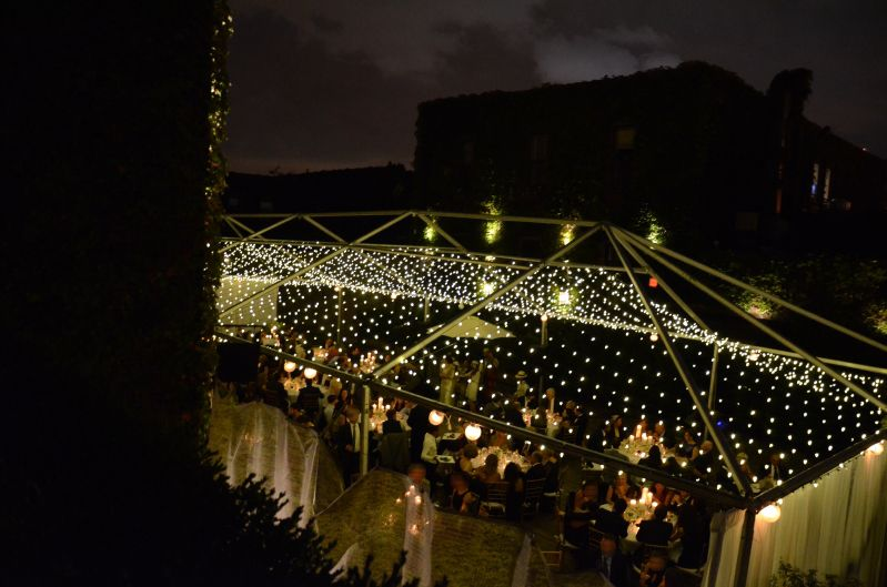 A canopy of String Lights suspended under tent frame in the rear courtyard at The Foundry located in Long Island City, New York
