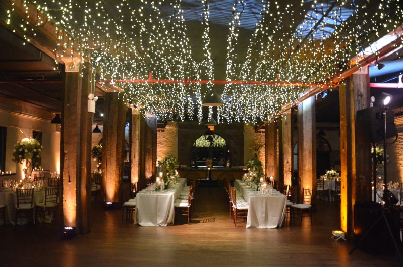 Uplights placed at the base of each column and along perimeter walls with icicle fairy lights suspended above dance floor on 1st floor at The Liberty Warehouse located in Brooklyn, NY