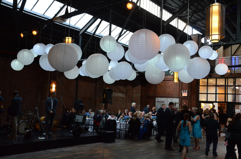Paper lanterns with a decorative LED light inside suspended in a cluster at 26 Bridge located in Brooklyn, New York