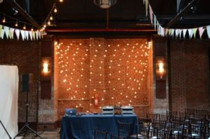 String Lights with multiple swoops against wall with pennant flags suspended at 26 Bridge located in Brooklyn, New York