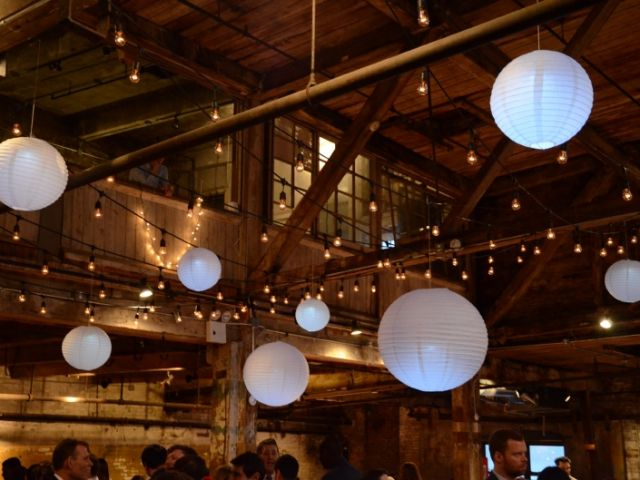The Greenpoint Loft (Brooklyn, NY) - 300ft of String Lights with S14 bulbs suspended in  a zigzag pattern with Paper Lanterns under half  of the high ceiling area on the main floor.