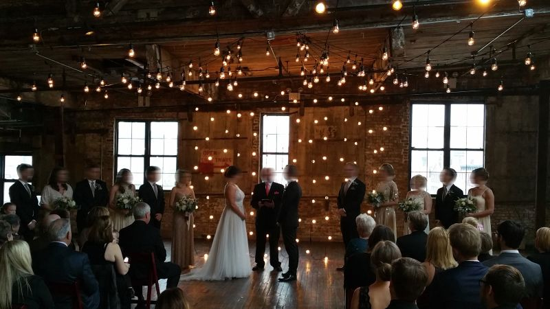 String Lights suspended vertically as a backdrop behind ceremony and overhead at The Greenpoint Loft located in Brooklyn, New York