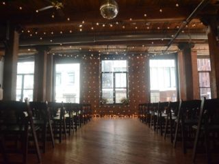 The Dumbo Loft (Brooklyn, New York) - String Lights suspended Vertically as a backdrop behind ceremony with String Lights suspended in a zigzagging pattern between center columns