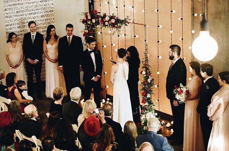 String Lights suspended vertically against wall behind ceremony