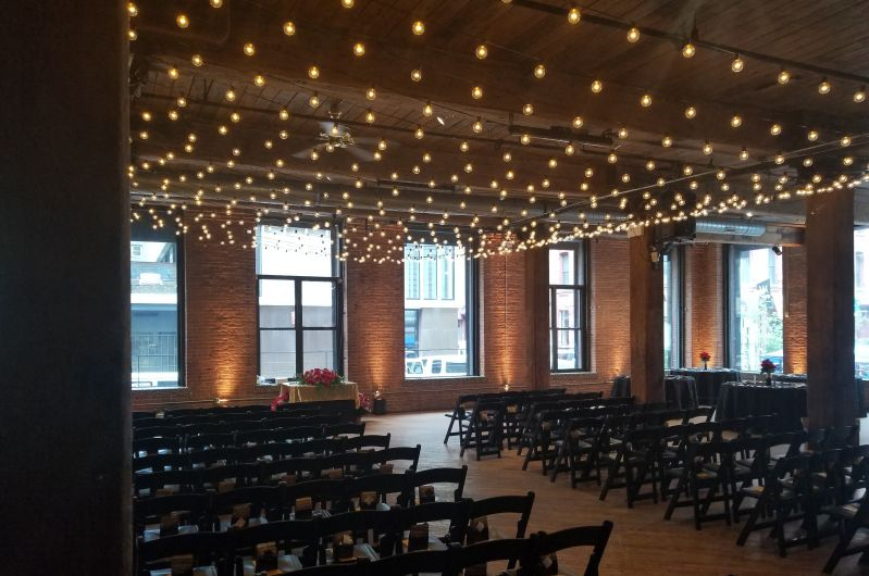 A canopy of String lights suspended between center columns over ceremony are with warm white up-lights placed at the base of each column between windows for a wedding at The Dumbo Loft located in Brooklyn New York