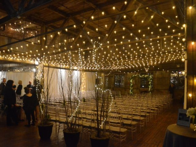 A canopy of String Light suspended between center columns at The Greenpoint Loft along with String Lights wrapped around center columns.