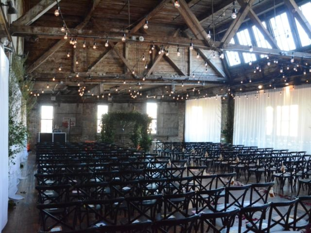 String Lights suspended between center columns with white sheer curtains partitioning the ceremony area at The Greenpoint Loft