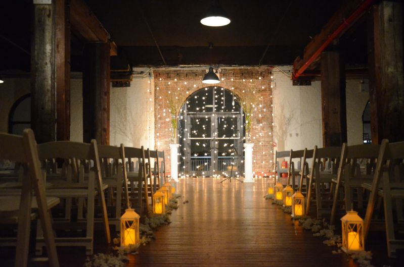 Spot light on Ceremony area w/ vertical String Light suspened as a backdrop at The Liberty Warehouse