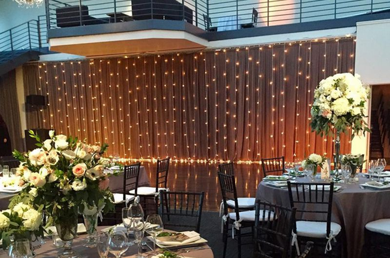 String Lights suspended vertically as backdrop against wall for a wedding at The Tribeca Rooftop located in New York City